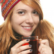 Young smiling womwith winter cap warming-up with tea — Stock Photo #6675279