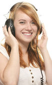 Laughing redhead girl with headphones listening to music — Stock Photo