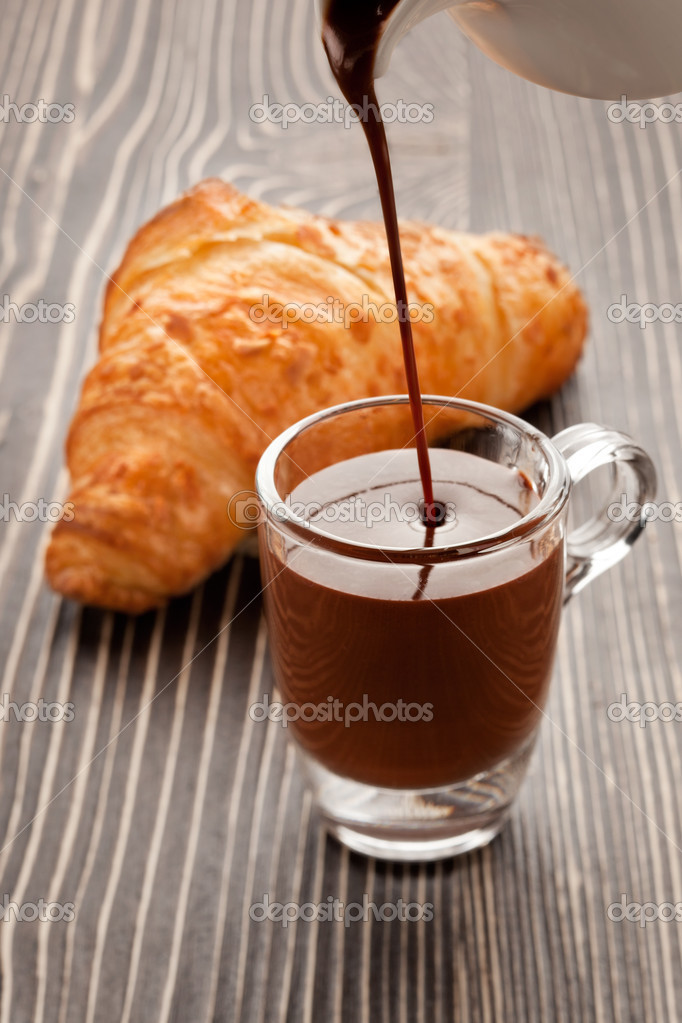 A picture of crunchy croissant and cup of hot chocolate pouring from pot. — Stock Photo #6122483