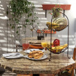 Semi outdoor tropical cafe table with fruit juice and croissants - Stock Photo