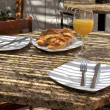 Semi outdoor tropical cafe table with juice and croissants — Foto de Stock