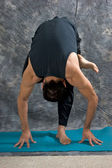 Man doing one legged forward fold — Stock Photo