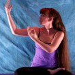 Woman in half lotus yoga with hands in dancing shiva position — Stock Photo