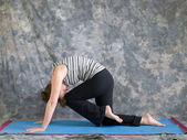 Woman doing Yoga posture Marjaryasana variation or strong cat po — Stock Photo