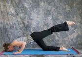 Woman doing Yoga posture sunbird pose left — Stock Photo