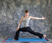 Woman doing Yoga posture rotated high lunge — Stock Photo