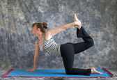 Woman doing Yoga posture Vyaghrasana The Tiger Pose variation — Stock Photo