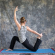 Woman doing Yoga posture King Arthurs pose variation — Stock Photo