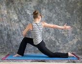 Woman doing Yoga posture rotated Low Lunge or Ashwa Sanchalanasa — Stock Photo