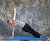 Woman doing Yoga posture Vasisthasana or side plank pose — Stock Photo