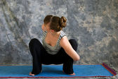 Young woman doing Yoga posture bound Malasana or garland squat p — Stock Photo