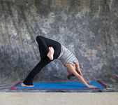 Young woman doing Yoga posture Eka Pada Adho Mukha Svanasana or — Stock Photo