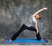 Woman doing Yoga posture extended side angle pose — Stock Photo