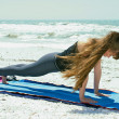 Woman doing yoga exercise on beach in high plank pose — Stock fotografie