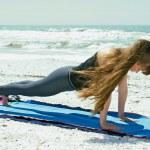 高い板のポーズでビーチでのヨガの練習をやっている女性 — ストック写真