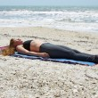 Woman doing yoga exercise on beach in Savasana or corpse pose — Foto Stock