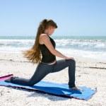 mujer haciendo ejercicio de yoga en la playa rotado estocada baja o ashwa sa — Foto de Stock