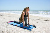 Woman doing yoga exercise low lunge pose on beach — Stock Photo
