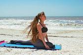 Woman doing yoga exercise on beach in Salamba Kapotasana or Supp — Stock Photo