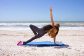 Woman doing yoga exercise on beach in Vasisthasana or side plank — Stock Photo