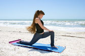 Woman doing yoga exercise on beach rotated Low Lunge or Ashwa Sa — Stock Photo