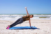 Young woman doing yoga exercise on beach in Vasisthasana or side — Stock Photo