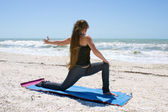 Young woman doing yoga exercise on beach rotated Low Lunge or As — Stock Photo
