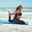 Beautiful woman doing yoga exercise on beach in Kapotasana or Pi — 图库照片