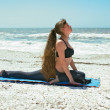 Woman doing yoga exercise on beach in Kapotasana or Pigeon Postu — Foto Stock