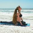 vrouw doen yoga oefening op strand in kapotasana of duif postu — Stockfoto #6142936