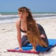 Woman doing yoga exercise on beach kneeling lotus pose — Stok fotoğraf