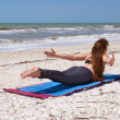 Woman doing yoga exercise on beach Shalabhasana or locust pose — Stock fotografie