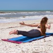 Woman doing yoga exercise on beach Shalabhasana or locust pose — Стоковое фото