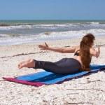 ビーチの shalabhasana またはバッタのポーズのヨガの練習をやっている女性 — ストック写真
