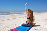 Woman doing yoga exercise on beach in bound half lotus pose or A — Stock Photo