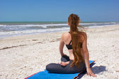 Woman doing yoga exercise on beach in rotated half lotus pose or — Stock Photo