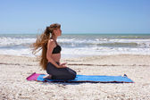 Woman doing yoga exercise on beach in Virasana or hero pose — Stock Photo