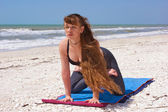 Woman doing yoga exercise on beach kneeling lotus pose — Stock Photo