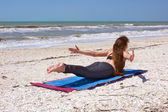Woman doing yoga exercise on beach Shalabhasana or locust pose — Stock Photo