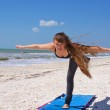 Woman doing yoga exercise airplane posture on beach — Стоковое фото #6153855