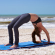 Woman doing yoga exercise full wheel pose on beach — Стоковое фото