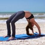 ビーチでのヨガ運動フル ホイール ポーズをやっている女性 — ストック写真