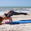 Woman doing yoga exercise Galavasana or sage pose on beach — Stock Photo