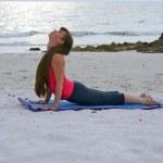 femme faire des exercices d'yoga face à la hausse chien posent sur la plage au soleil — Photo