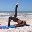 Young woman doing yoga exercise one leg bridge pose on beach — Стоковое фото #6154418