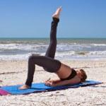 年轻女人在做瑜伽练习一条腿桥姿势上海滩 — 图库照片 #6154418