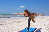 Woman doing yoga exercise airplane posture on beach — Stock Photo