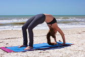 Woman doing yoga exercise full wheel pose on beach — Stock Photo
