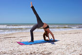 Woman doing yoga exercise one leg full wheel pose on beach — Stock Photo