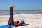 Woman doing yoga exercise reclined staff pose on beach — Stock Photo